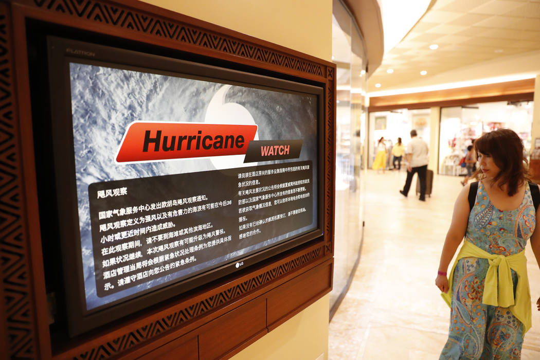 A shopper walks past a monitor displaying hurricane information in several different languages inside a hotel in Waikiki, Wednesday, Aug. 22, 2018, in Honolulu. (Marco Garcia/AP)