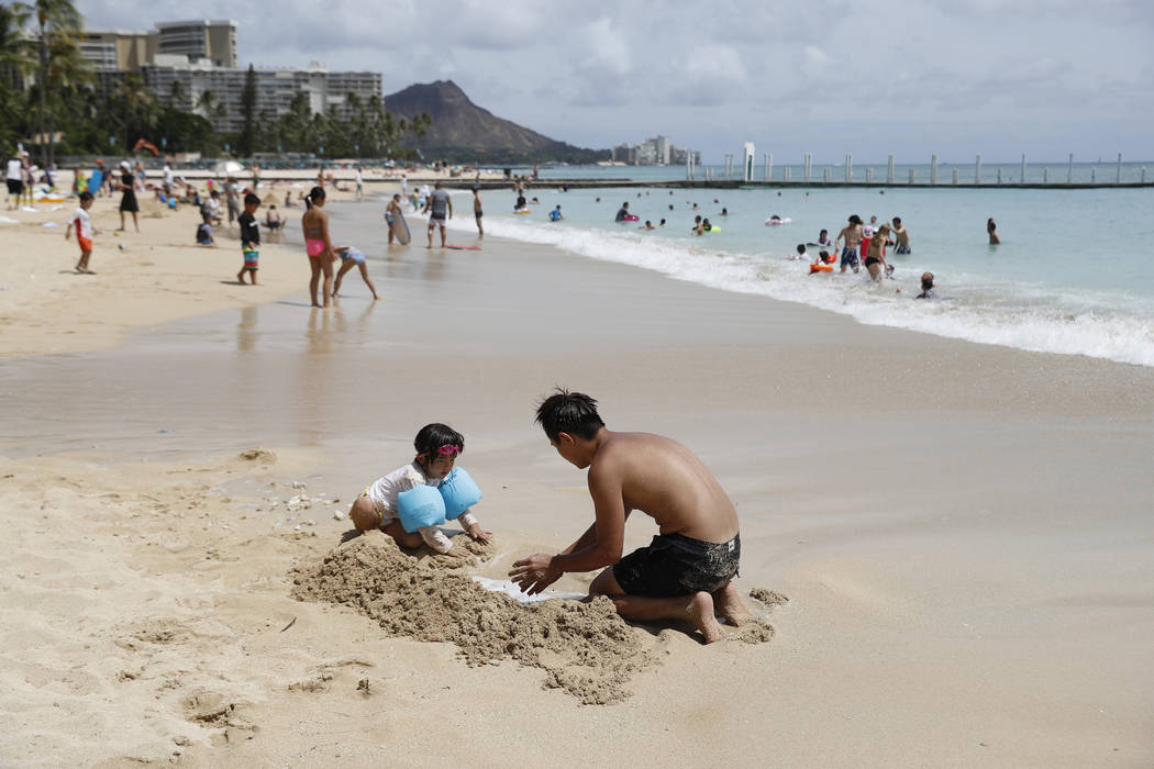 Beach goers frolic on Waikiki Beach, Wednesday, Aug. 22, 2018, in Honolulu. Hurricane Lane has weakened as it approaches Hawaii but was still expected to pack a wallop, forecasters said Wednesday. ...
