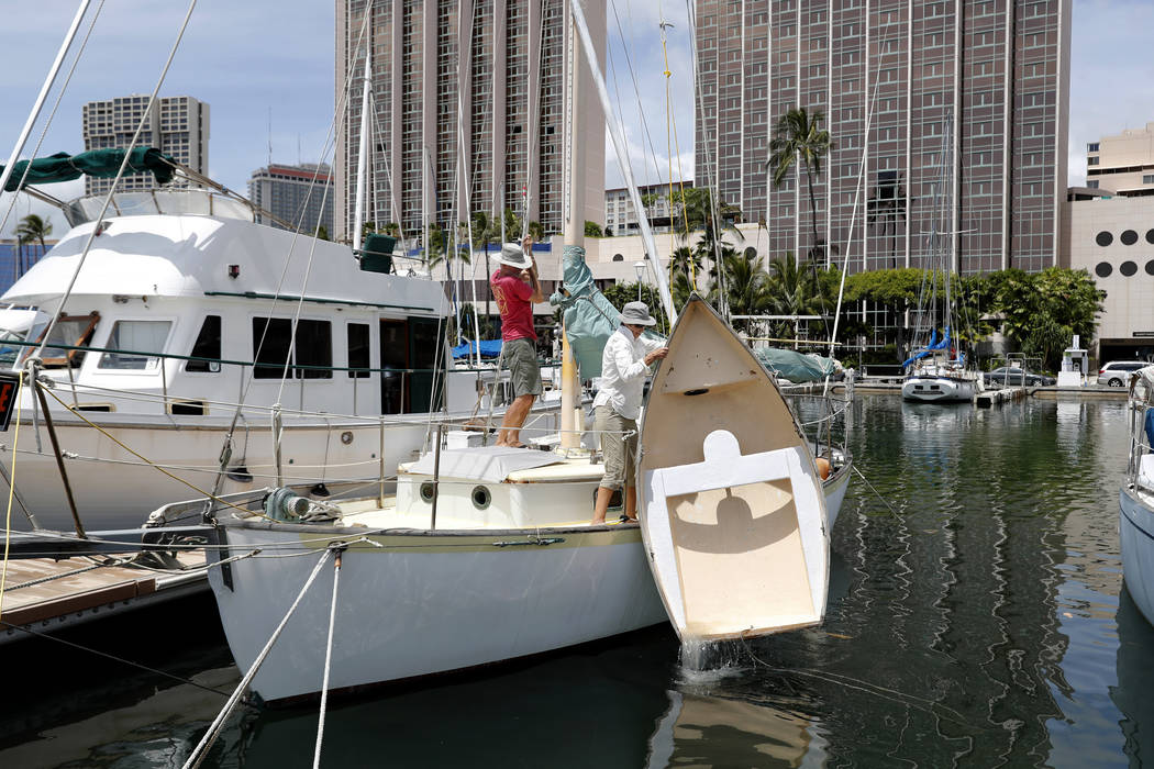 Rudy Kok, left, and Mary Kok pull their dingy out out of the harbor to secure to their sailing boat in preparation of Hurricane Lane, Wednesday, Aug. 22, 2018, in Honolulu. (Marco Garcia/AP)
