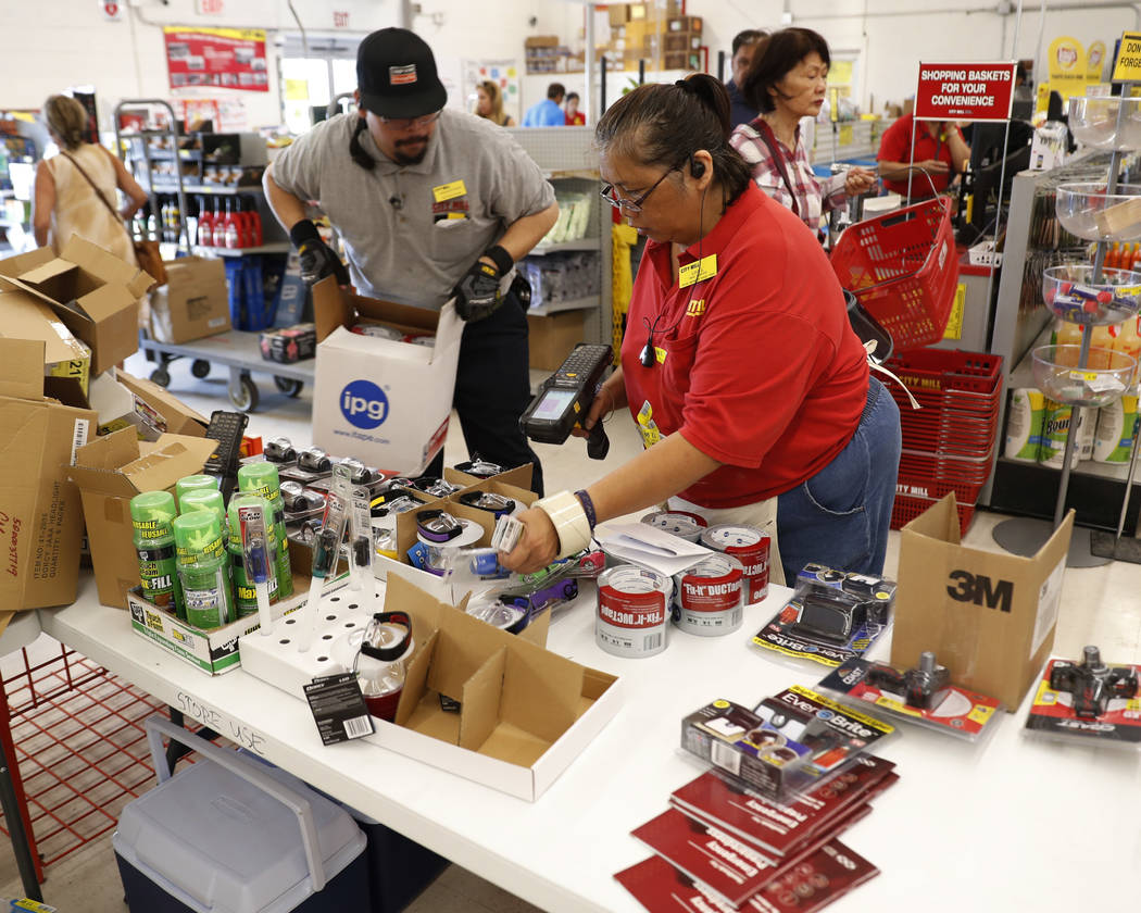 City Mill hardware store sales associates Frank Miller Gascon, left, Lisa Lavilla, fill a table up with hurricane supplies, Wednesday, Aug. 22, 2018, in Honolulu. (Marco Garcia/AP)