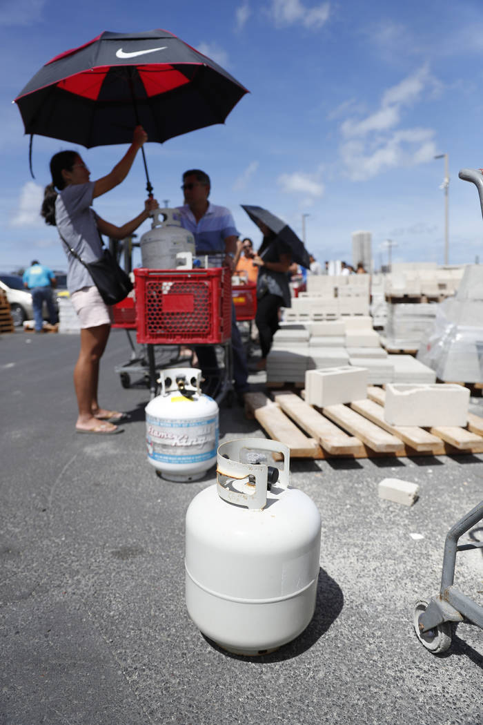 People stand in a line waiting to fill up propane tanks at a local hardware store, Wednesday, Aug. 22, 2018, in Honolulu. (AP Photo/Marco Garcia)