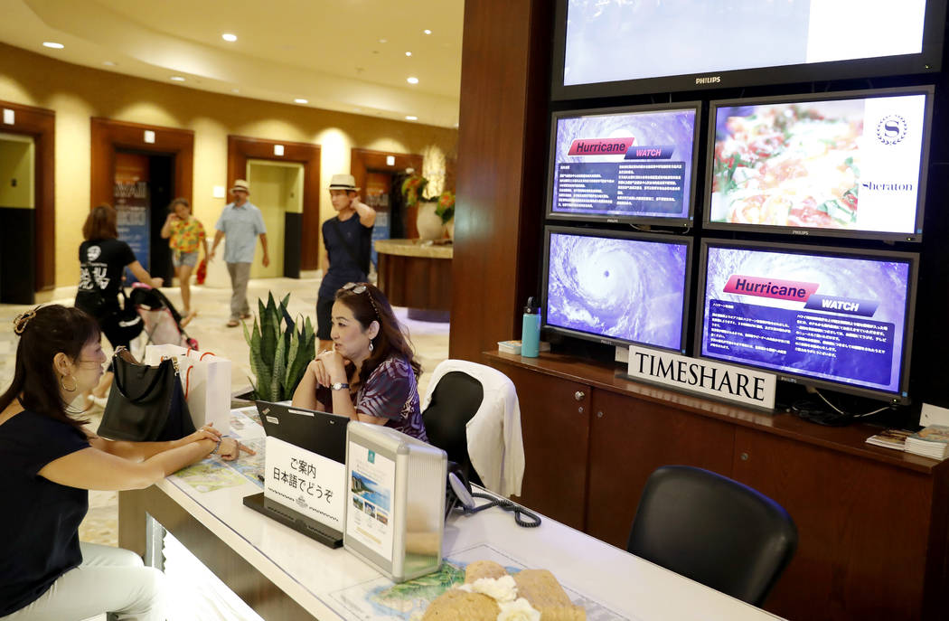 With several monitor displaying hurricane information in several different languages behind them, two women sit at a desk inside a Waikiki hotel, Wednesday, Aug. 22, 2018, in Honolulu. (AP Photo/ ...