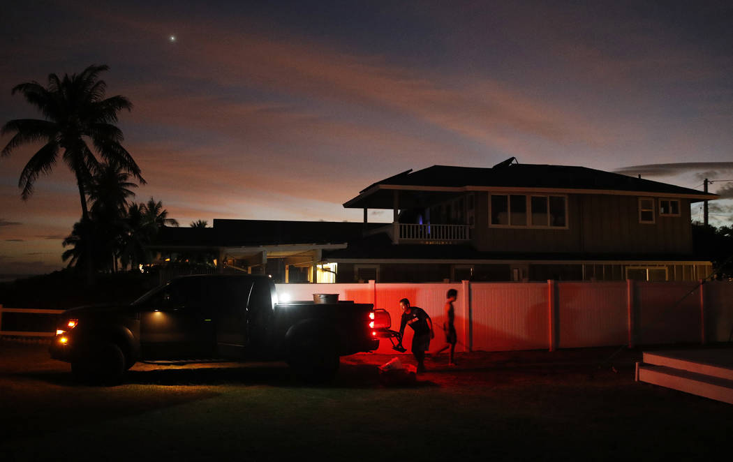 Jay Kitashima, left, loads up his truck after securing his tiny home in preparation for Hurricane Lane, Wednesday, Aug. 22, 2018, along Ewa Beach in Honolulu. As emergency shelters opened, rain be ...