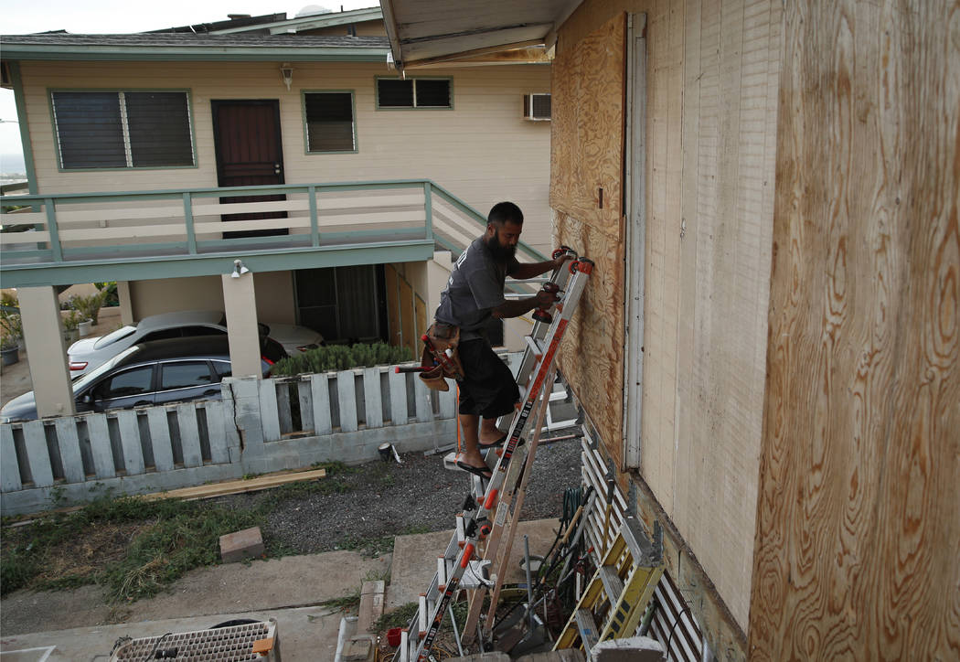 Kaipo Popa secures plywood to protect windows on a home in preparation for Hurricane Lane, Wednesday, Aug. 22, 2018, in Kapolei, Hawaii. As emergency shelters opened, rain began to pour and cellph ...