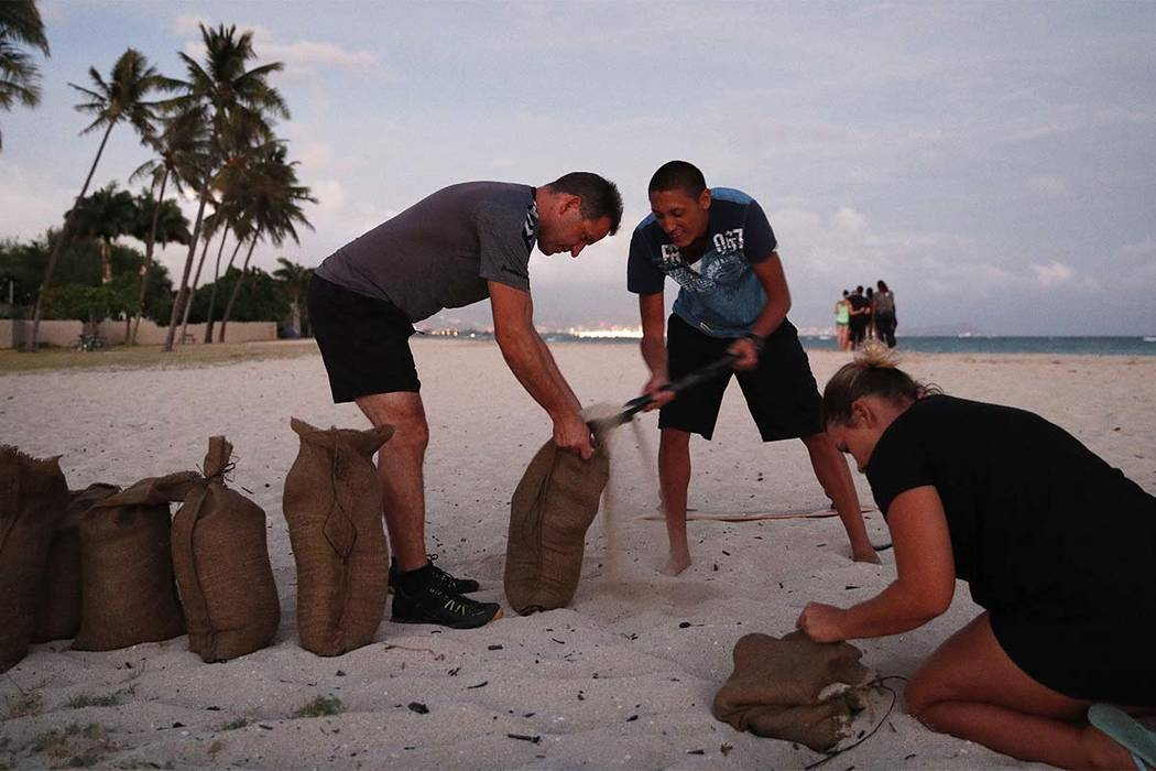 People, who declined to be named, fill up sand bags that will be used to help protect their home in preparation for Hurricane Lane, Wednesday, Aug. 22, 2018, along Ewa Beach in Honolulu. (John Loc ...