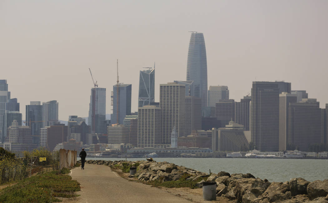 A man rides a scooter on Treasure Island as the San Francisco city skyline sits in a smoky haze in the background onAug. 8, 2018. (AP Photo/Lorin Eleni Gill, File)
