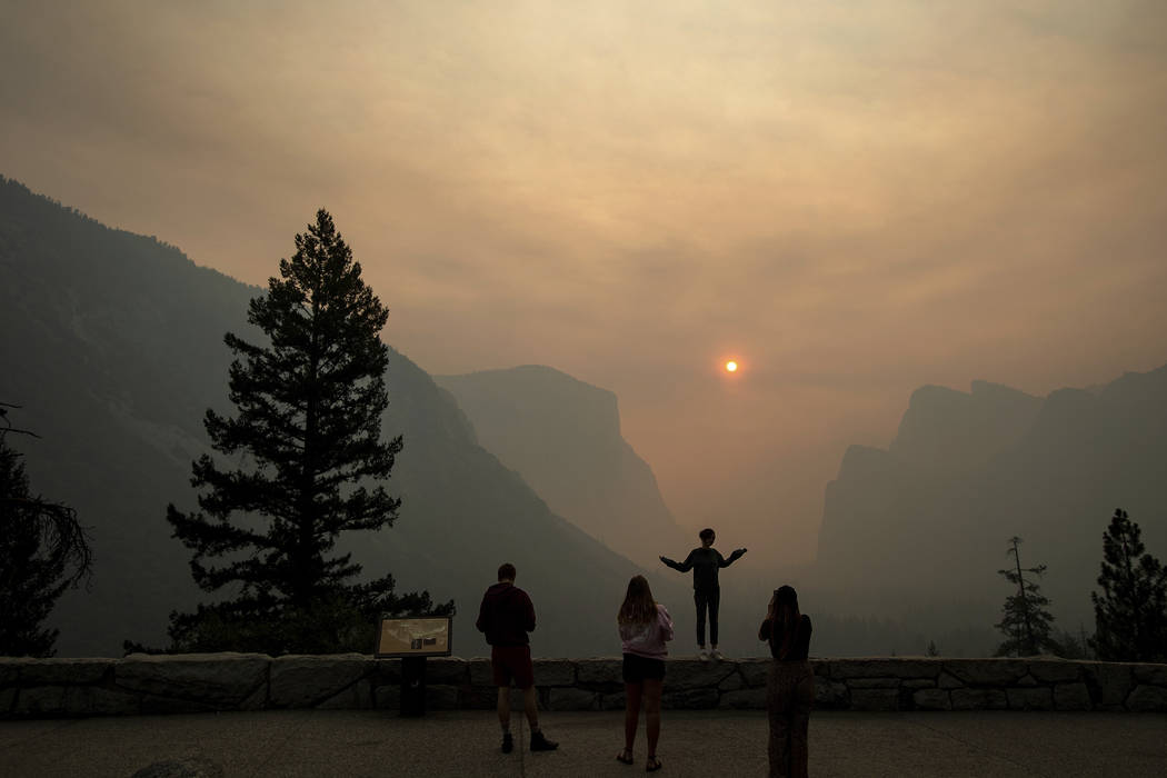 Hannah Whyatt poses for a friend's photo as smoke from the Ferguson fire fills Yosemite Valley in Yosemite National Park, Calif. on July 25, 2018. (AP Photo/Noah Berger, File)