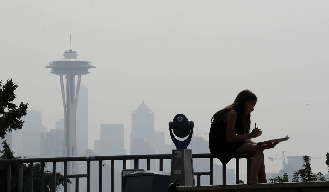 A girl works on a drawing next to an unused viewing scope as a smoky haze obscures the Space Needle and downtown Seattle behind on Aug. 14, 2018. (AP Photo/Elaine Thompson, File)