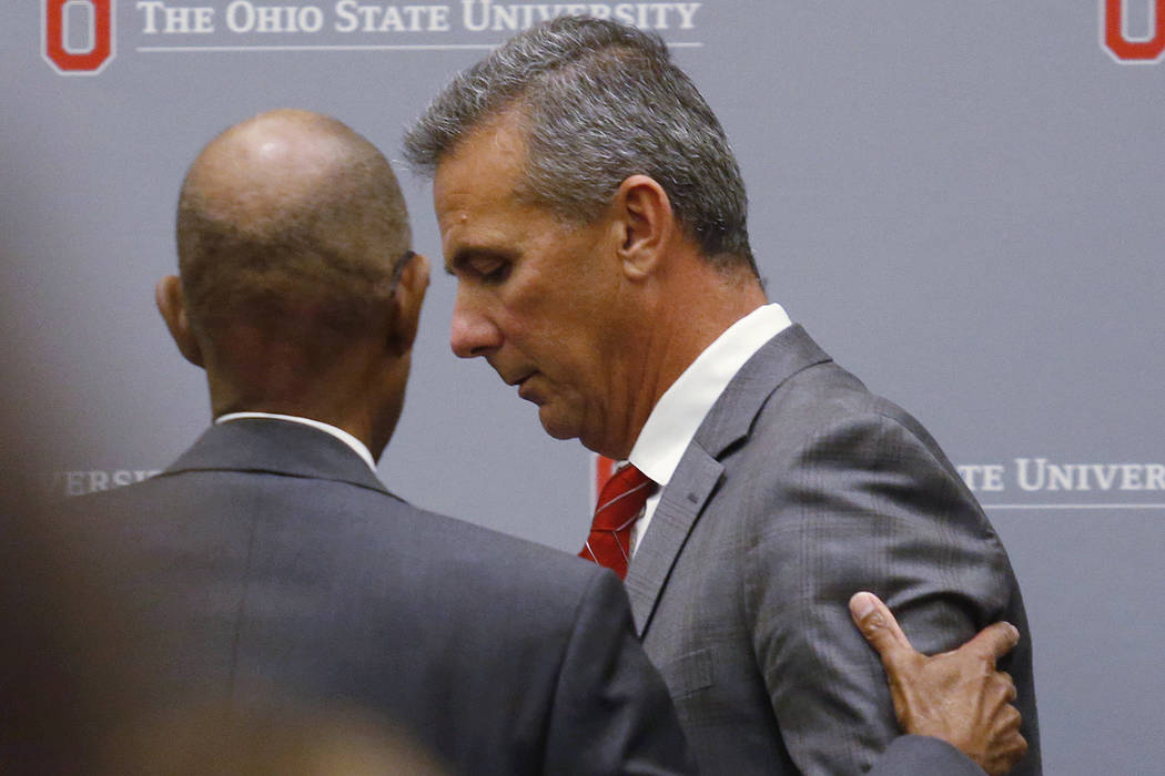 Ohio State University President Michael Drake offers words to football coach Urban Meyer, who leaves the stage following a news conference in Columbus, Ohio, Wednesday, Aug. 22, 2018. Ohio State s ...
