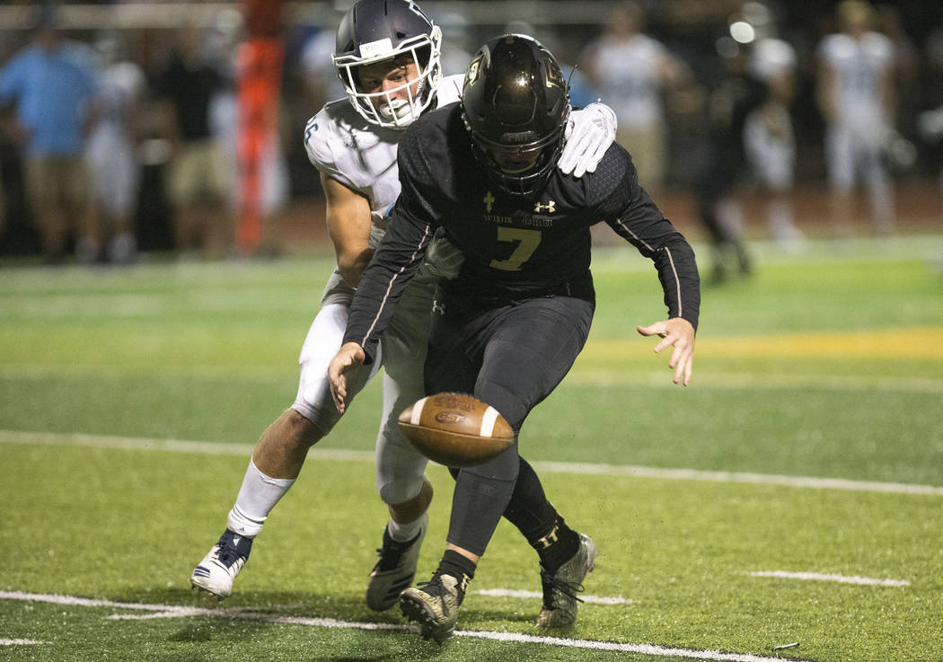 Faith Lutheran quarterback Sagan Gronauer (7) loses control of the ball after getting tackled by Valor Christian's (Colorado) Payton Polson (36) during the second half of varsity football game at ...
