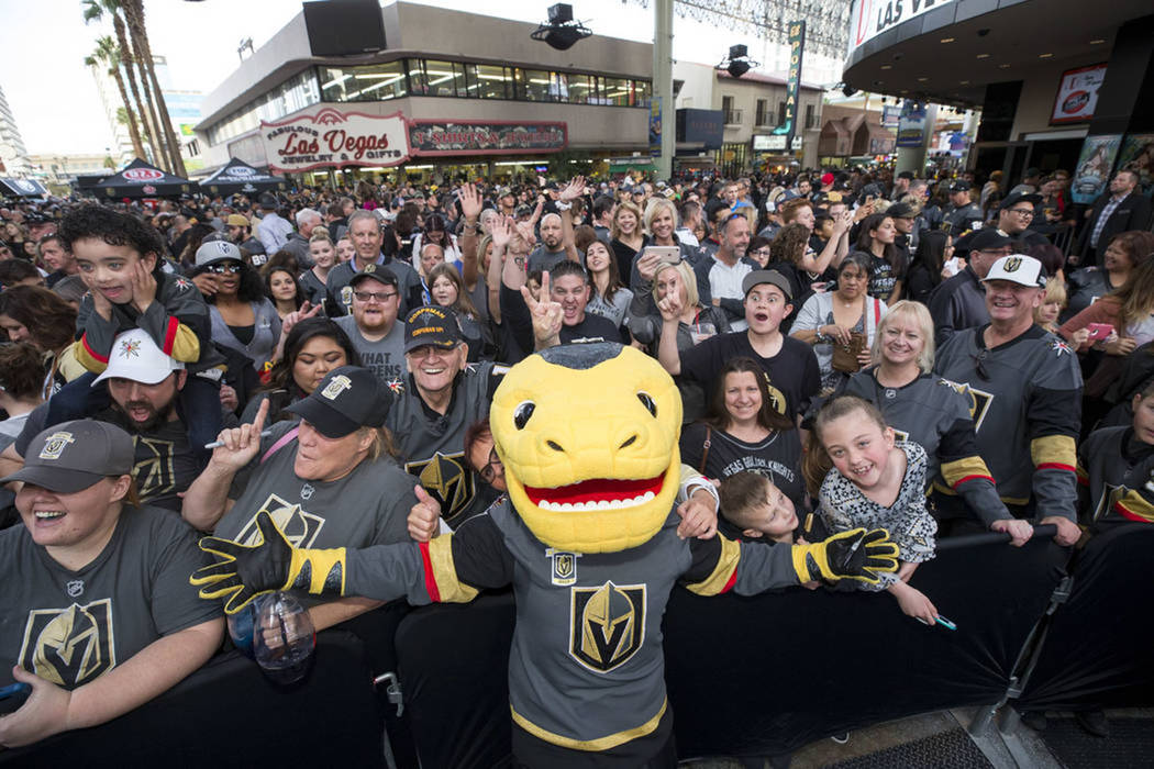 The Vegas Golden Knights mascot Chance the Golden Gila Monster poses with fans during the team's first fan fest at the Fremont Street Experience in downtown Las Vegas on Sunday, Jan. 14, 2018. (Ri ...