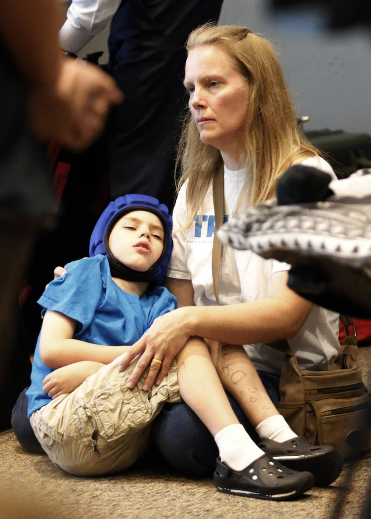 Medical-marijuana advocate Heather Nelson and her son Matthew, 10, listen during a news conference with opponents of Utah's medical marijuana ballot initiative as they lay out their case why voter ...