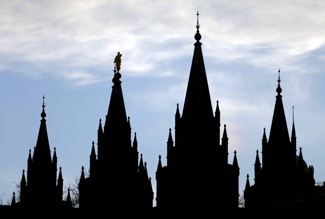The angel Moroni statue, silhouetted against the sky, sits atop the Salt Lake Temple, at Temple Square in Salt Lake City. (AP Photo/Rick Bowmer)