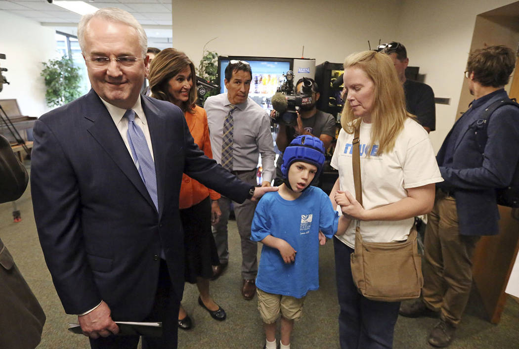 Jack Gerard, left, a leader in The Church of Jesus Christ of Latter-day Saints, speaks with Heather Nelson and her son Matthew, 10, following a news conference with opponents of Utah's medical mar ...
