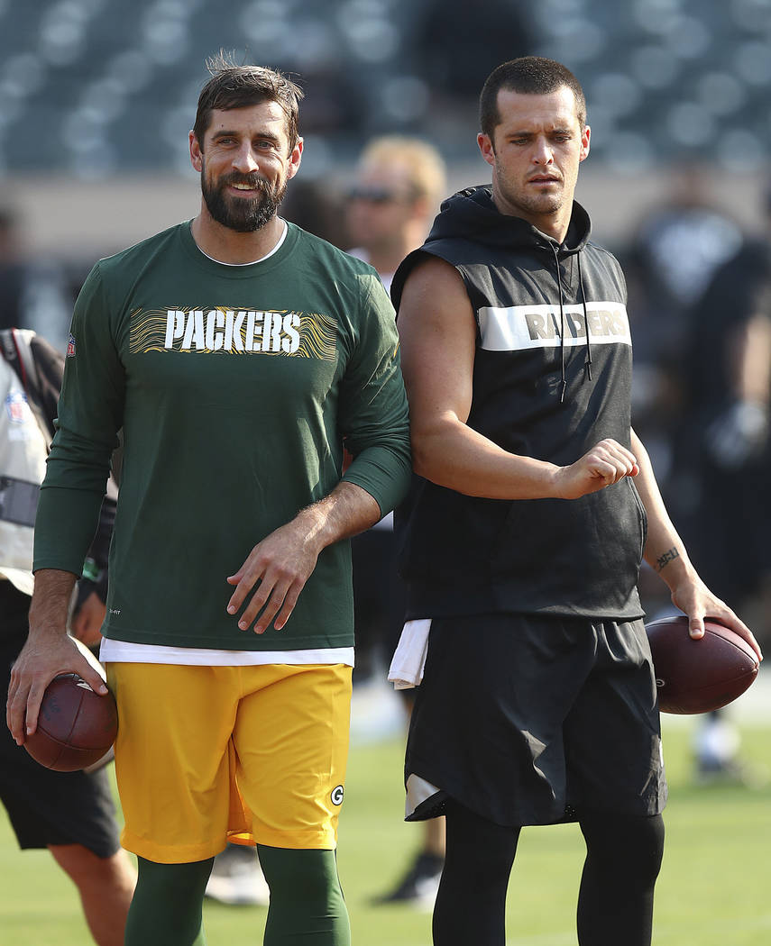 Green Bay Packers quarterback Aaron Rodgers, left, talks with Oakland Raiders quarterback Derek Carr before an NFL preseason football game in Oakland, Calif., Friday, Aug. 24, 2018. (AP Photo/Ben ...