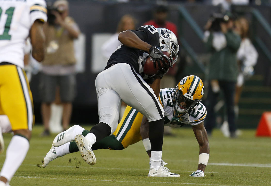 Oakland Raiders wide receiver Amari Cooper, top, runs against Green Bay Packers cornerback Jaire Alexander (23) an NFL preseason football game in Oakland, Calif., Friday, Aug. 24, 2018. (AP Photo/ ...