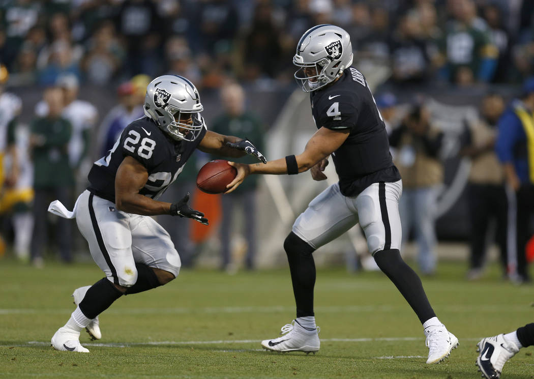 Oakland Raiders quarterback Derek Carr (4) hands off to running back Doug Martin (28) during the first half of an NFL preseason football game in Oakland, Calif., Friday, Aug. 24, 2018. (AP Photo/D ...