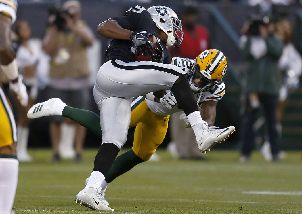 Oakland Raiders wide receiver Amari Cooper, top, runs against Green Bay Packers cornerback Jaire Alexander during the first half of an NFL preseason football game in Oakland, Calif., Friday, Aug. ...