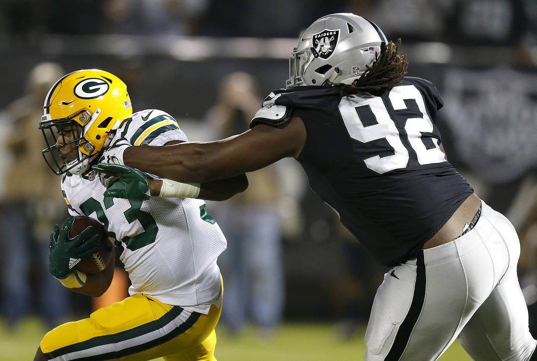 Green Bay Packers running back Aaron Jones (33) carries as Oakland Raiders nose tackle P.J. Hall (92) reaches for him during the first half of an NFL preseason football game in Oakland, Calif., Fr ...