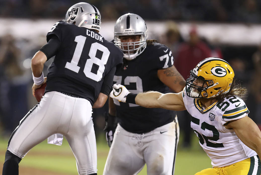 Green Bay Packers linebacker Clay Matthews (52) applies pressure to Oakland Raiders quarterback Connor Cook (18) during the first half of an NFL preseason football game in Oakland, Calif., Friday, ...