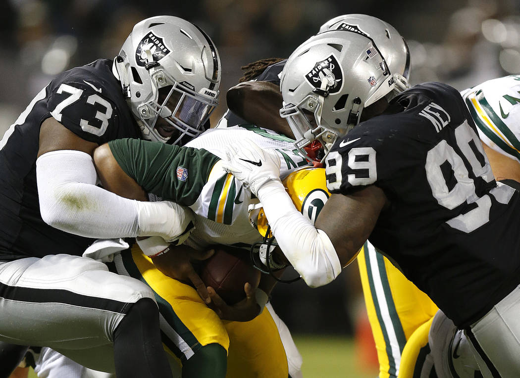 Green Bay Packers quarterback Brett Hundley, center, is sacked by Oakland Raiders defensive tackle Maurice Hurst (73) and defensive end Fadol Brown, obscured, during the first half of an NFL prese ...