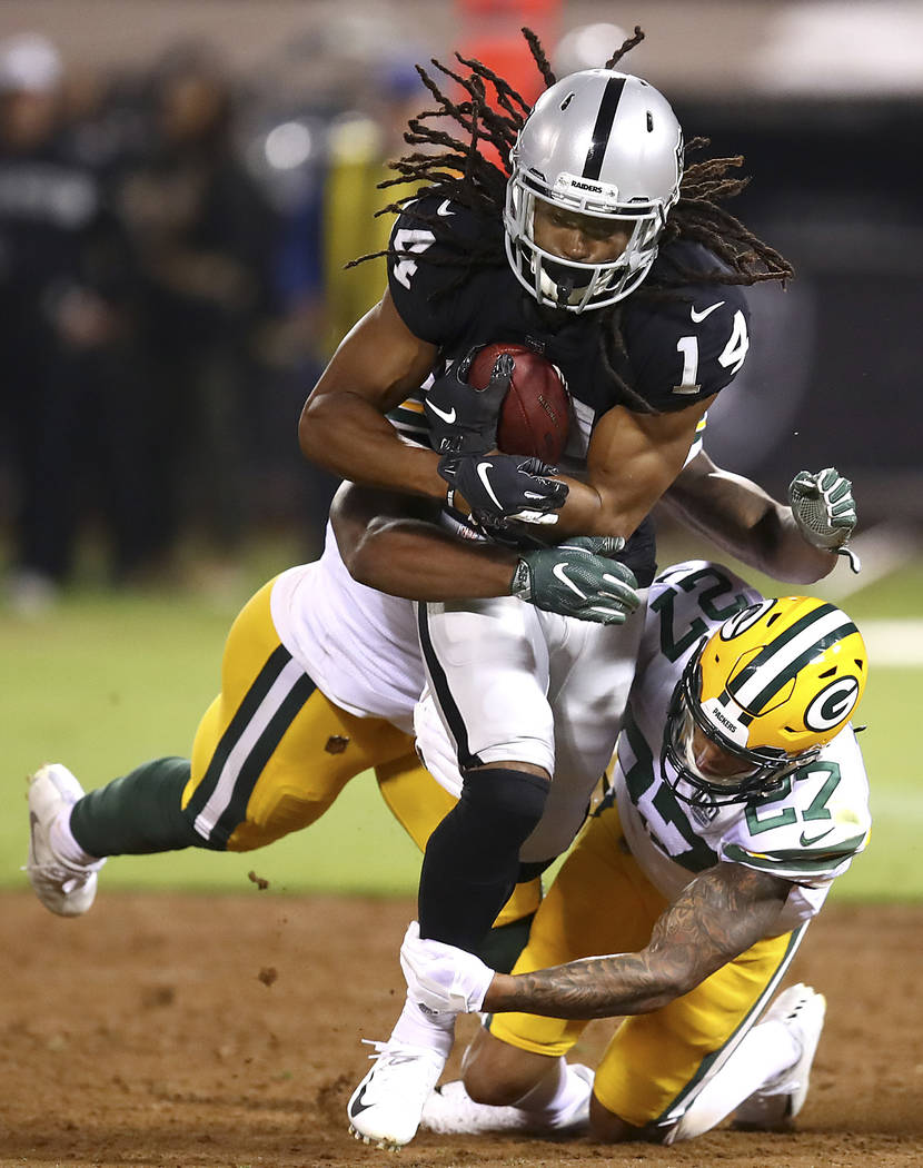 Oakland Raiders wide receiver Keon Hatcher (14) is tackled by Green Bay Packers safety Josh Jones (27) and linebacker Ahmad Thomas, rear, during the first half of an NFL preseason football game in ...