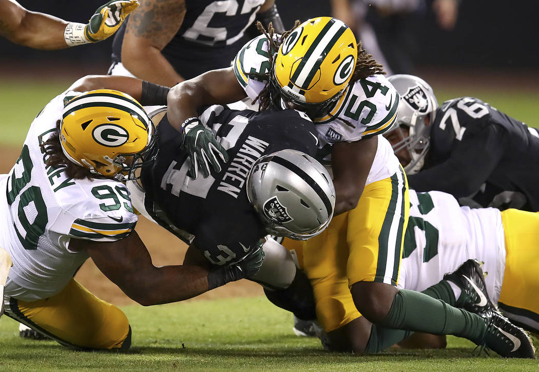Oakland Raiders running back Chris Warren III, center, is tackled by Green Bay Packers defensive end James Looney (99) and linebacker James Crawford (54) during the second half of an NFL preseason ...