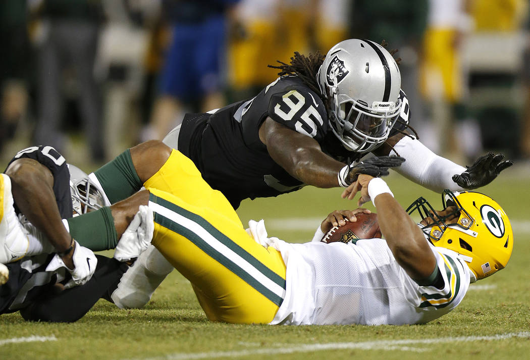 Oakland Raiders defensive end Fadol Brown (95) dives toward Green Bay Packers quarterback DeShone Kizer, bottom right, after Kizer was sacked by Raiders linebacker Nicholas Morrow, left, during th ...