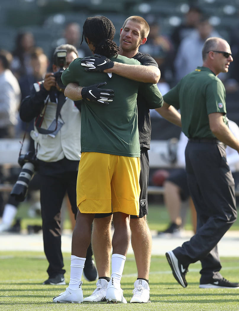 Oakland Raiders wide receiver Jordy Nelson, facing, hugs Green Bay Packers wide receiver Davante Adams before an NFL preseason football game in Oakland, Calif., Friday, Aug. 24, 2018. (AP Photo/Be ...