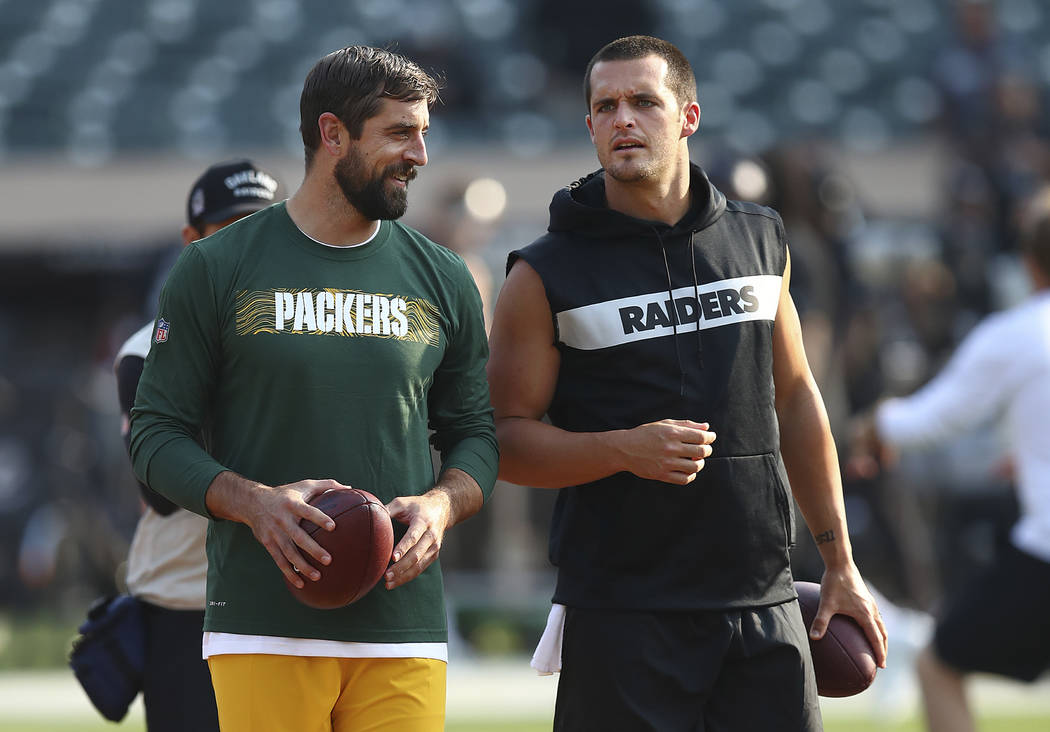 Green Bay Packers quarterback Aaron Rodgers, left, talks with Oakland Raiders quarterback Derek Carr before an NFL preseason football game between the Raiders and the Packers in Oakland, Calif., F ...
