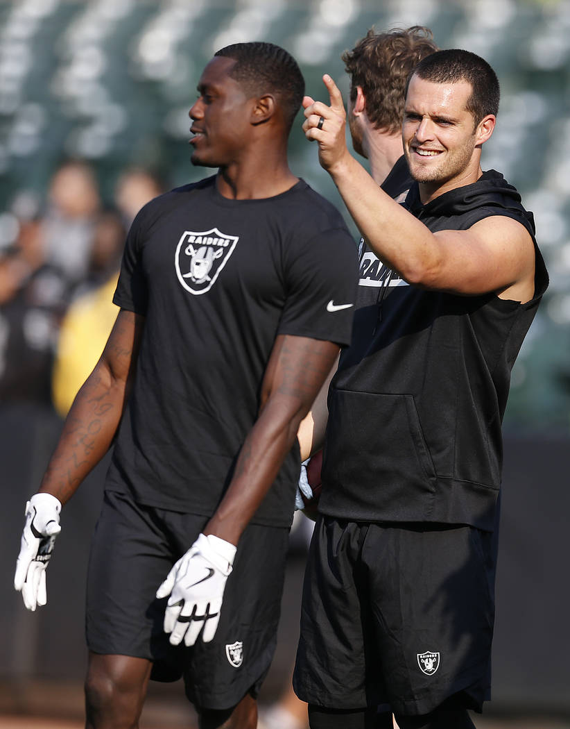 Oakland Raiders quarterback Derek Carr, right, gesture while warming up before an NFL preseason football game against the Green Bay Packers in Oakland, Calif., Friday, Aug. 24, 2018. (AP Photo/D. ...