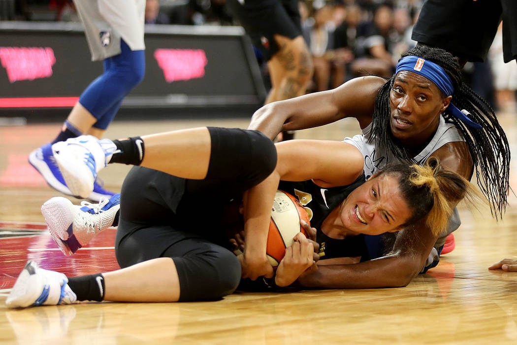 Las Vegas Aces guard Kayla McBride (21) grabs the ball from Minnesota Lynx players center Sylvia Fowles (34) at a WNBA basketball at the Mandalay Bay Events Center in Las Vegas, Sunday, June 24, 2 ...