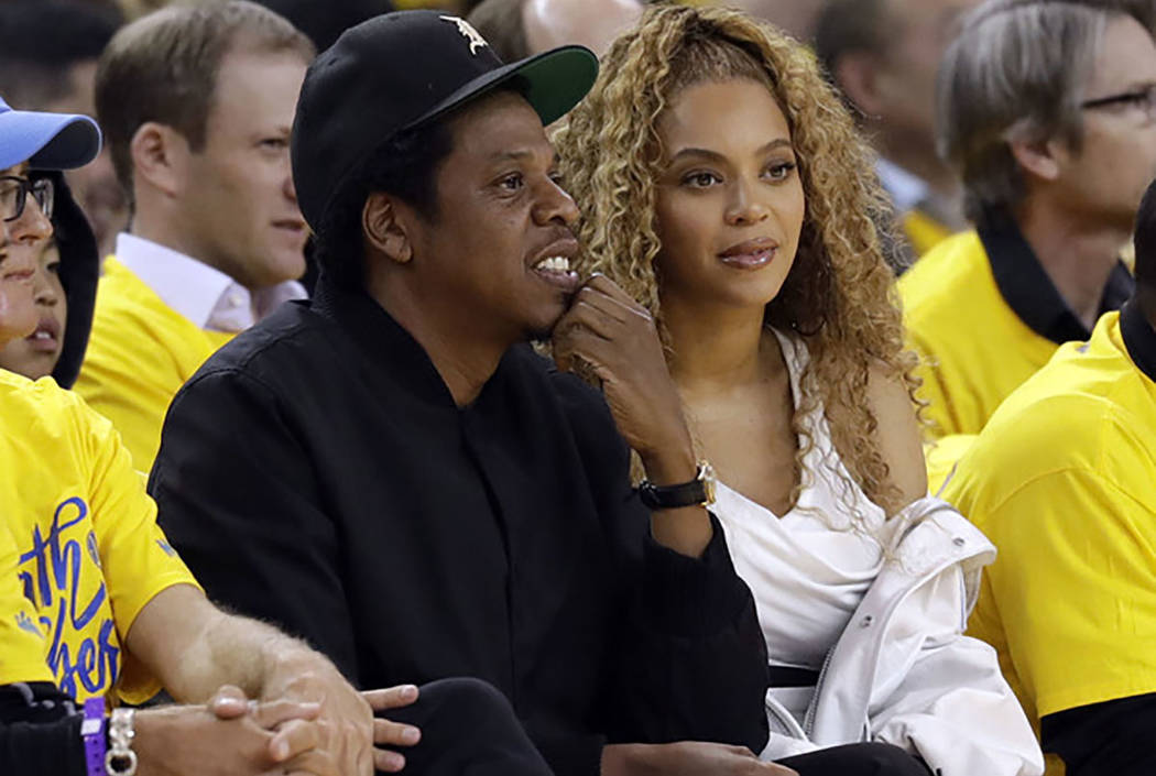 Jay-Z and Beyonce watch a NBA playoff game between Golden State and New Orleans Pelicans in Oakland, Calif., in April 2018. (AP Photo/Marcio Jose Sanchez)