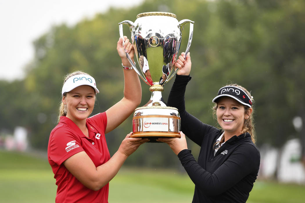 Canada's Brooke Henderson holds the trophy with her sister and caddie Brittany as she celebrates her win at the Women's Canadian Open golf tournament in Regina, Saskatchewan, Sunday Aug. 26, 2018. ...