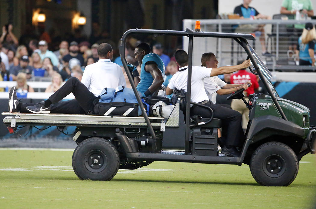 Jacksonville Jaguars wide receiver Marqise Lee, center, is taken off the field after he was injured during the first half of the team's NFL preseason football game against the Atlanta Falcons, Sat ...