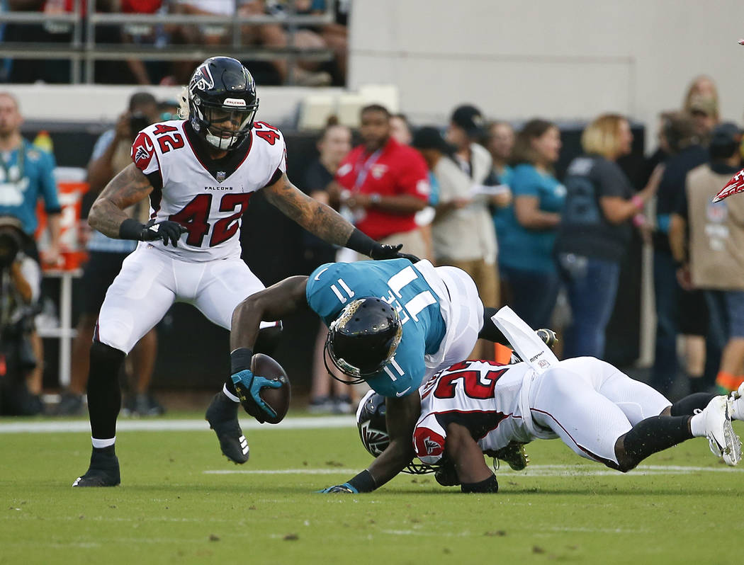 Jacksonville Jaguars wide receiver Marqise Lee (11) is injured as he is tackled by Atlanta Falcons cornerback Damontae Kazee, right, and linebacker Duke Riley (42) during the first half of an NFL ...