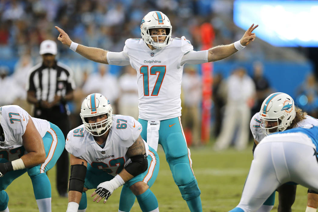 In this Aug. 17, 2018, file photo, Miami Dolphins' Ryan Tannehill (17) calls a play at the line of scrimmage, behind center Daniel Kilgore (67) in the first half of an NFL football game against th ...