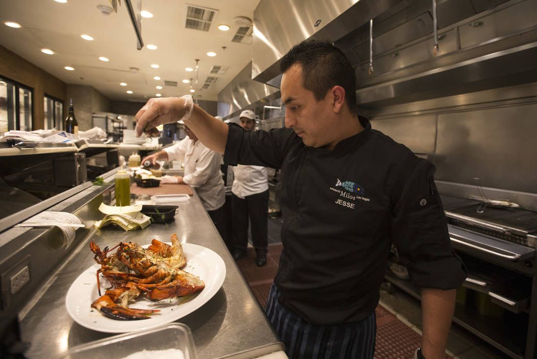 Chef Jesse Maldonado prepares the Deep Sea Bay of Fundy, grilled lobster, garnished with extra-virgin olive oil and lemon juice served with Greek fried potatoes at Estiatorio Milos inside The Cosm ...