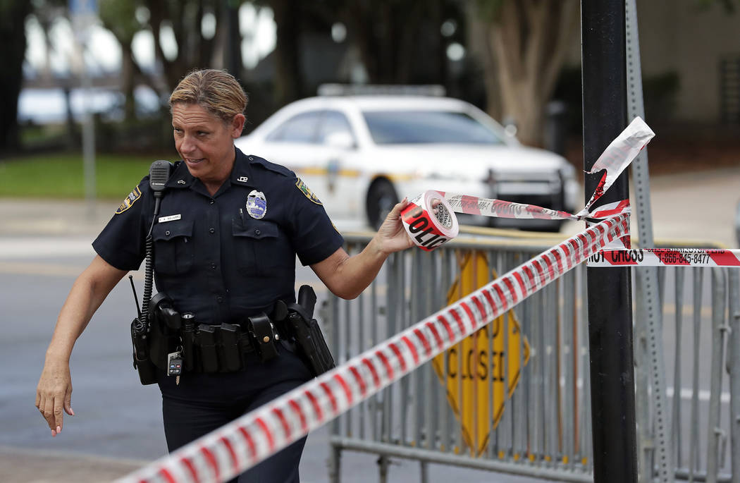 A Jacksonville police officer blocks off an area Monday, Aug. 27, 2018, near the scene of a fatal shooting at The Jacksonville Landing on Sunday in Jacksonville, Fla. A gunman opened fire at a vid ...
