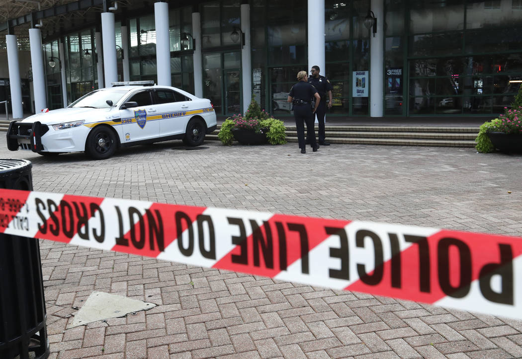 Jacksonville police officers guard an area Monday, Aug. 27, 2018, near the scene of a fatal shooting at The Jacksonville Landing on Sunday in Jacksonville, Fla. A gunman opened fire at a video gam ...