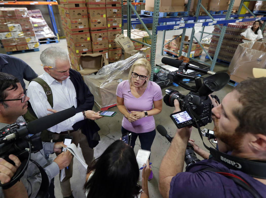 In this Tuesday, Aug. 21, 2018 photo, U.S. Senatorial candidate U.S. Rep. Kyrsten Sinema, D-Ariz., speaks with the media after volunteering at a food pantry in Phoenix. Sinema is the democratic no ...