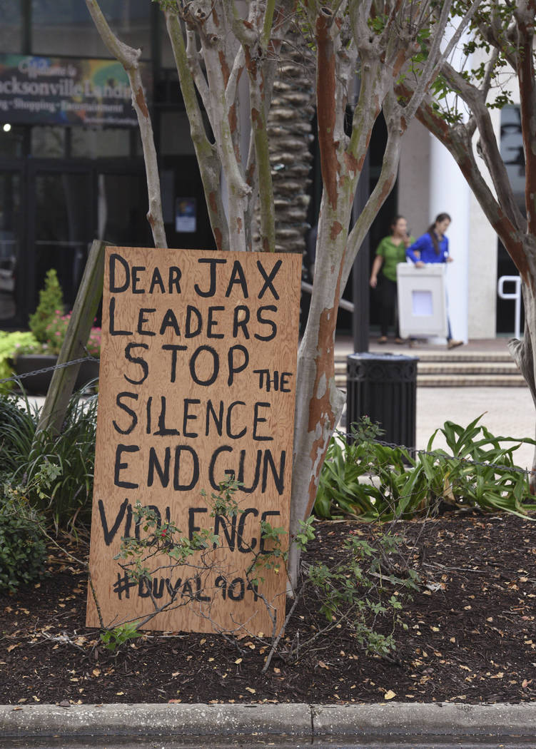 A local faith leader placed signs in front of the Jacksonville Landing Monday morning following the mass shooting there on Sunday at the Jacksonville Landing in downtown Jacksonville, Fla., Monday ...