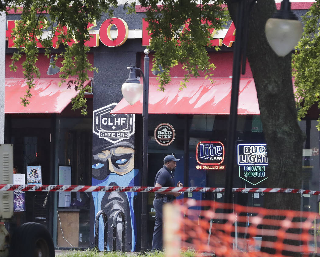 A police officer walks by the front of a Chicago Pizza and GLHF Game Bar on Monday, Aug. 27, 2018, at the scene of fatal shooting on Sunday, at The Jacksonville Landing in Jacksonville, Fla. A gun ...