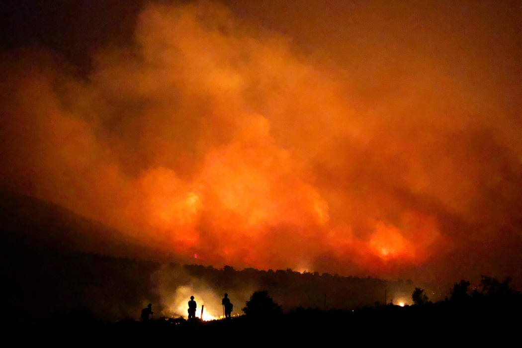 Firefighters are silhouetted by flames from the South Sugarloaf Fire in northern Elko County on Thursday. U.S. Forest Service