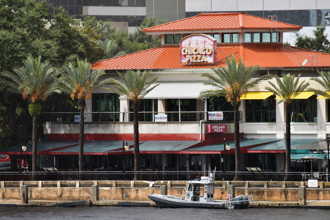 Law enforcement boats patrol the St. Johns River at The Jacksonville Landing after a mass shooting during a video game tournament at the riverfront mall, Sunday, Aug. 26, 2018, in Jacksonville, Fl ...