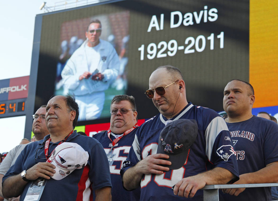New England Patriots fans pause for a moment of silence in honor of Oakland Raiders owner Al Davis, who died Saturday, before the Patriots faced the New York Jets in an NFL football game in Foxbor ...