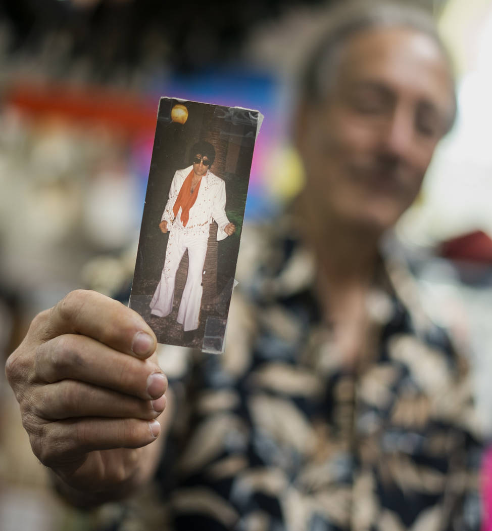 Martin Sadowitz, owner of American Costumes, holds up a photo of himself wearing an Elvis costume in the 80s in Las Vegas, Tuesday, Aug. 28, 2018. After 40 years of business, American Costumes wil ...