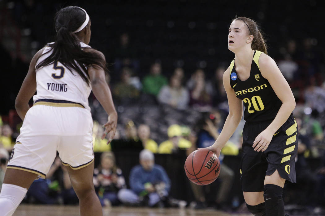 Oregon guard Sabrina Ionescu (20) dribbles the ball while defended by Notre Dame guard Jackie Young (5) during the first half in a regional final at the NCAA women's college basketball tournament, ...