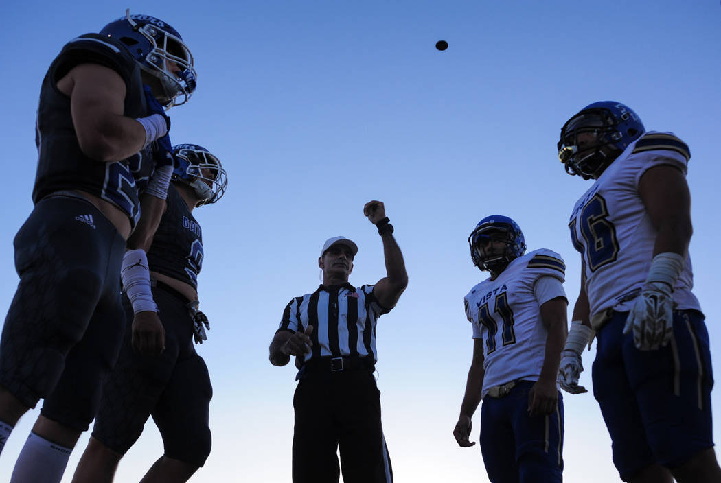 Referee Joe Molinaro flips the coin to decide kickoff between the Green Valley captains, left, and the Sierra Vista captains, right, at Green Valley High School in Henderson on Friday, Aug. 31, 20 ...