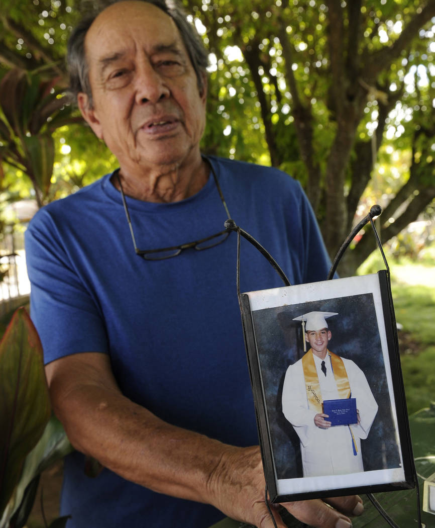 In this Monday, July 10, 2017 file photo, Clifford Kang, father of soldier Ikaika Kang, poses with a 2001 photo of his son in Kailua, Hawaii. Ikaika Kang is set to plead guilty Wednesday, Aug. 29, ...